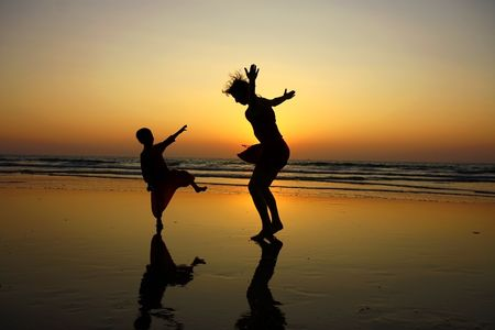 niños cocinando: silueta de la madre y su hijo en la playa durante la puesta de sol