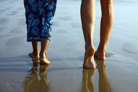 detail of child and girl legs walking on the beach Stock Photo