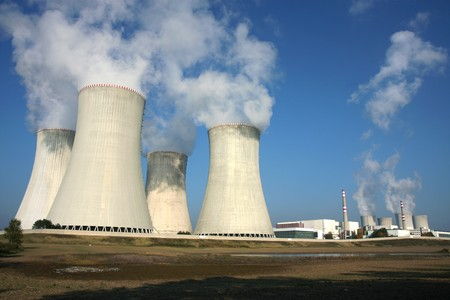 nuclear waste: smoking power plant in agriculture field under blue sky