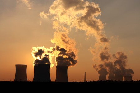 chimney and cooling towers of power plant during sunset Stock Photo