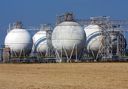 petrochemical: white rounded oil tanks and agriculture field