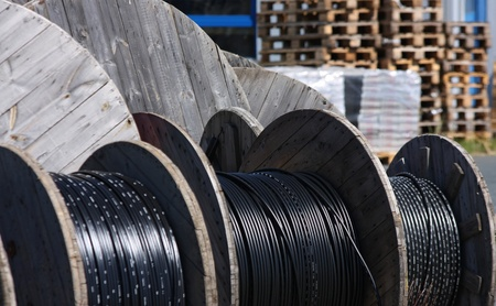 long  black telephone cables on wooden spool