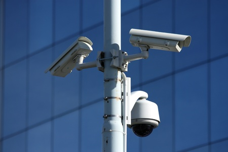 video surveillance: three security cameras on front of glass building
