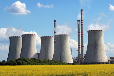 global cooling: view of coal power plant over yellow agriculture field
