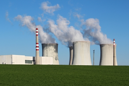 radiacion: planta de energía nuclear en el campo verde