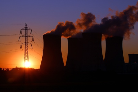 high voltage tower and power plant chimney during sunset photo