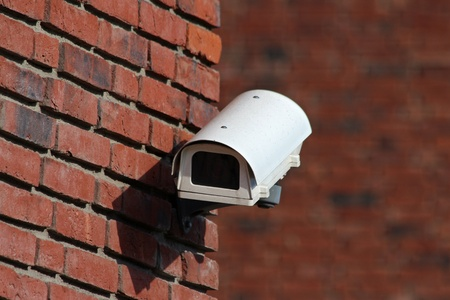 security cctv camera on brick wall facade photo