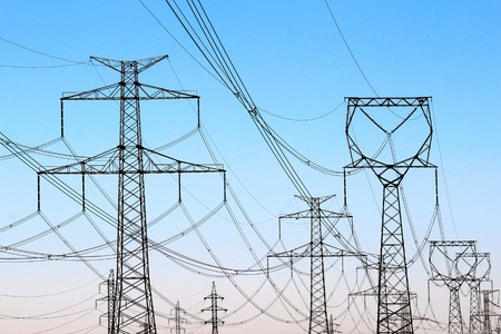 jungle of high voltage  power electricity pylons under sky Stock Photo