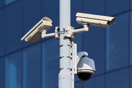 při pohledu na fotoaparát: tři CCTV bezpečnostní kamery na ulici pylonu Reklamní fotografie
