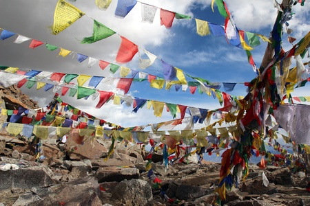 buddhism prayer belief: colourfull praying buddhist flags under cloudy sky