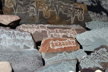 detail of written mantra on buddhist mani stones photo
