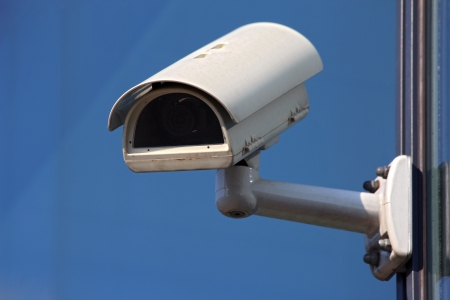 close circuit camera: white cctv security camera on blue background