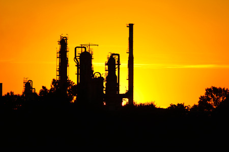 silhouette of  oil refinery factory  against sunset photo