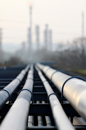 crude oil pipeline and oil  refinery against light Stock Photo