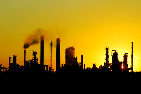 carbon pollution: black silhouette of big crude oil refinery from Russia