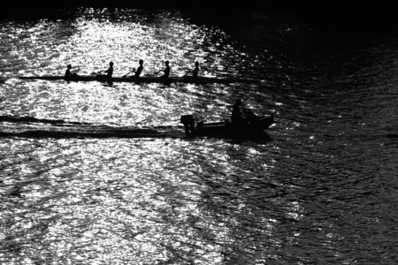 boat with four rowers and helmsman on river water photo