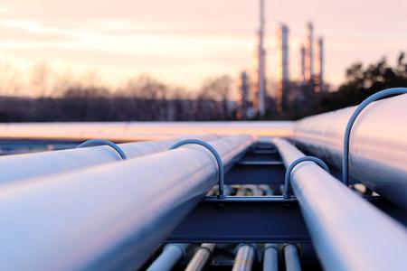 Stalowe długie rury w fabryce ropy naftowej podczas zachodu słońca