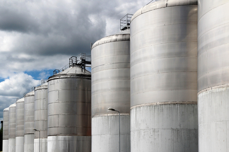 large stainless steel fermentation vessel under cloudy sky Stock Photo