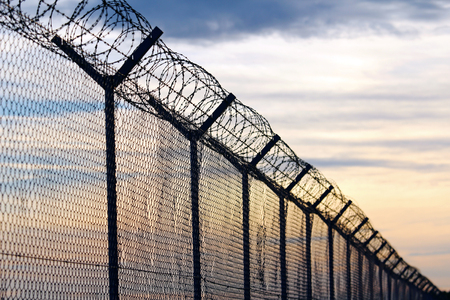 Silhouette of Barbed Wire fence against a Cloudy Sky Stock Photo - 73338855