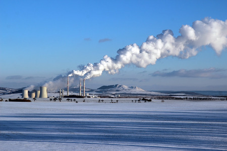 snowy landscape with steaming coal power plant Stock Photo
