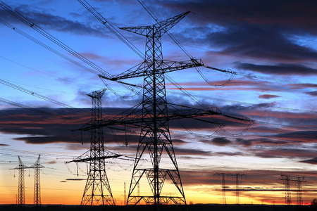 Silhouette of electricity pylons during sunset Stock Photo