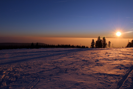 sunset in mountains and fog in wintertime