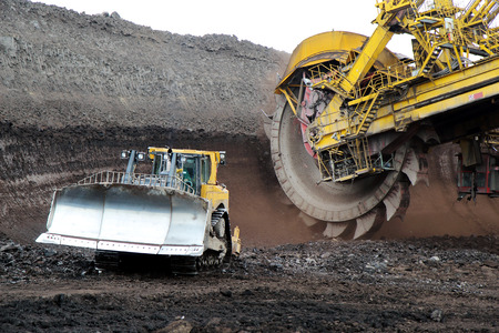 bulldozer and huge mining excavator wheel in brown coal mine