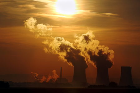 sun set over smoking nuclear power plant Stock Photo