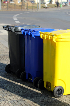 three different multicolored dustbins on the street