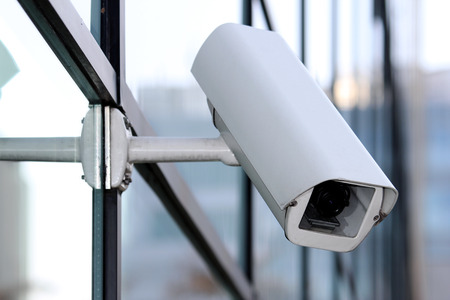 white security cctv camera on glass facade