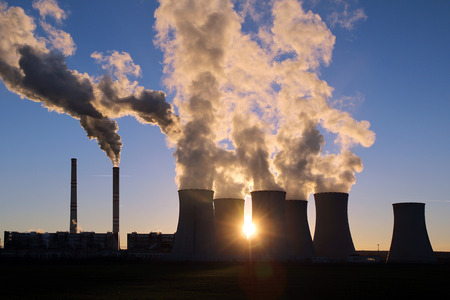 smoking cooling towers of coal power plant against the sun Stock Photo