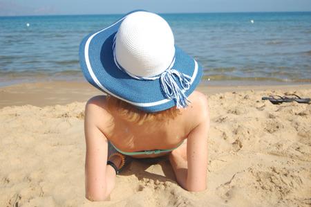 Young lady sunbathing on the sandy beach of the Tyrrhenian sea