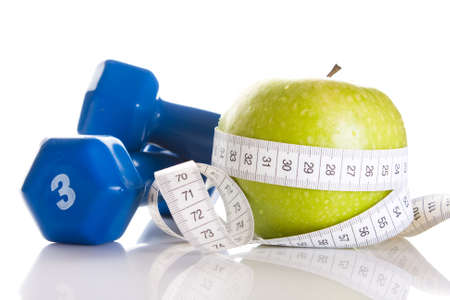 dumbbells, fresh green apple and measure tape photo