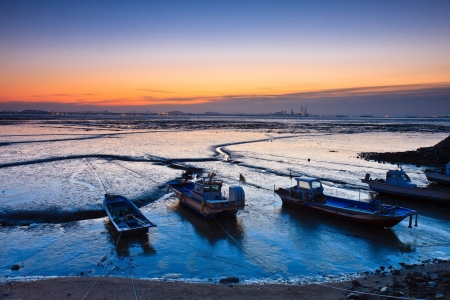 Landscape of mud flat with boats by twilight