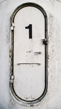 Dirty white oval metal door with the number 1 written on it photo