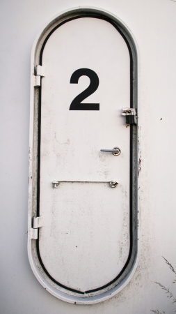 Dirty white oval metal door with the number 2 written on it photo