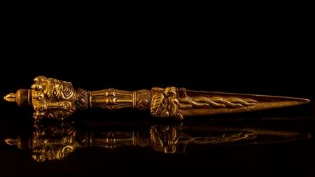 exorcism: kila  Buddhism  Tibetan knife  The kila, or phurba, is a ritual three sided knife associated with the meditational deity Vajrakilaya  On black background Stock Photo