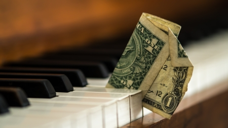 earned: Dirty old one dollar bill stuck in a piano - Hard times being a musician