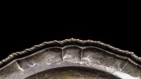 specular: RRIM de un viejo disco de la porci�n de plata con p�tina sobre fondo negro que muestra los detalles especulares Foto de archivo