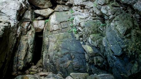 Dark entrance into a granite cave