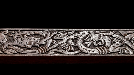 carving: Viking wood carving depicting two fire breathing dragons fighting Stock Photo
