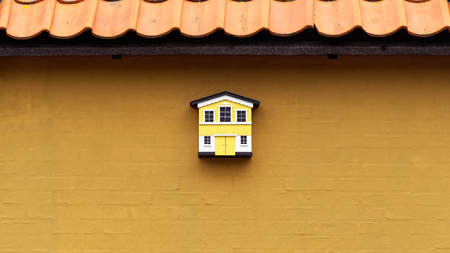 birdhouse: small yellow and whtite birdhouse on a curry yellow wall Stock Photo