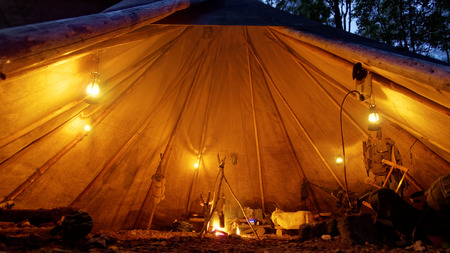 camp fire: cozy tipi interior with oil lamps and camp fire Stock Photo
