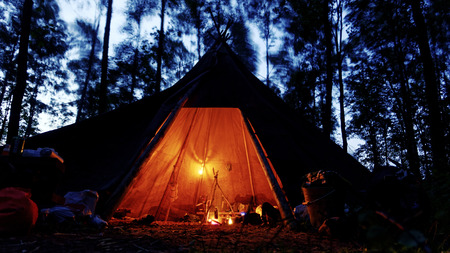 tipi: cozy tipi with oil lamps and camp fire in a dark and stormy forest Stock Photo