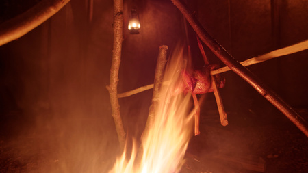tipi: Chicken roasting on a spear over a campfire Stock Photo