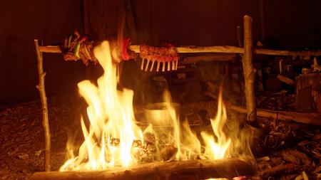 tipi: lamb crown roasting along side beef on a campfire inside a tipi