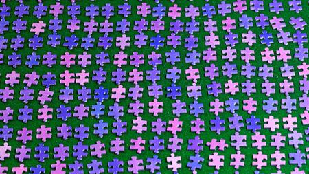 piezas de rompecabezas: piezas del rompecabezas de color p�rpura ordenados cuidadosamente en un pa�o de mesa verde
