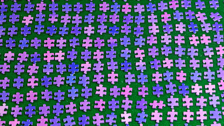 sorted: purple puzzle pieces neatly sorted on a green table cloth