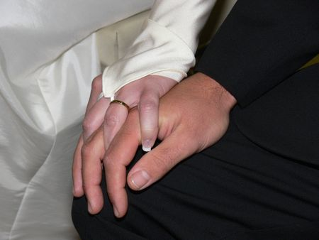 couple holding hands during wedding