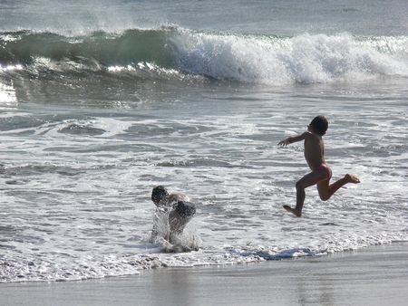 kinderen springen in de golven, Azoren Stockfoto